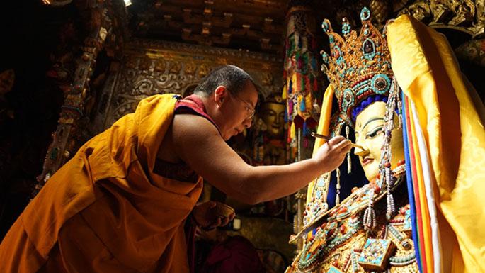 3图 班禅为十二岁释迦牟尼等身佛像面部涂绘金粉。摄影:王淑.jpg