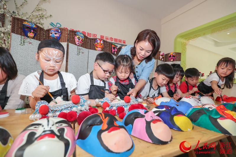 第一幼儿园的戏曲表演专用教室,老师们正在给戏曲化妆班的孩子画脸谱.
