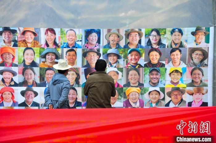 图为当地民众在观看展板上的笑脸。 张伟 摄