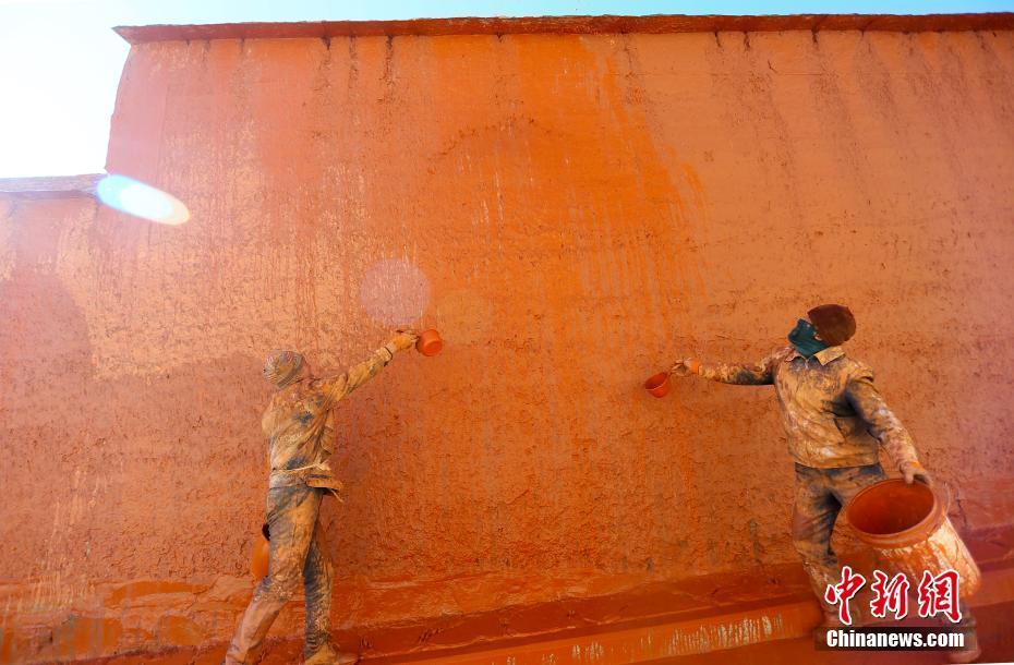 拉卜楞寺用传统泼洒法为寺院墙壁